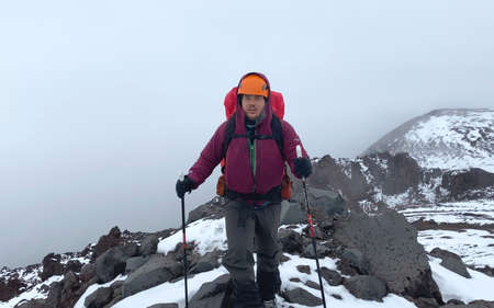 Tired tourist with a backpack and trekking poles walks along a mountain trail. Mountain climbing. Trekking in the Klyuchevskoy volcano park. Travel to the Kamchatka Peninsula. 写真素材
