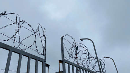 Fence with barbed wire against the gray sky. Protected area. Imprisonment concept.