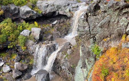 Close-up of amazing two-stage waterfall. Stunning autumn landscape. Beautiful place. Travel to the Kamchatka Peninsula.