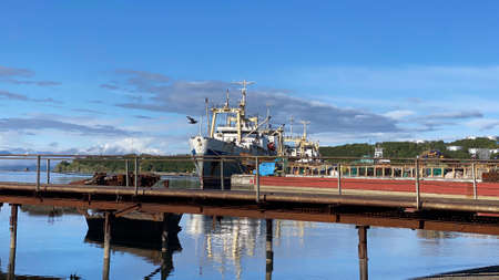Old ship at the pier in the port. The seaport of Petropavlovsk-Kamchatsky. Beautiful blue sea. Mountains, hills, volcanoes and ships of Kamchatka. 写真素材