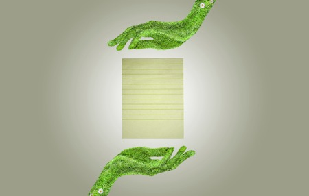 Paper in his hand, ecology symbol concept, hand covered with green grass photo
