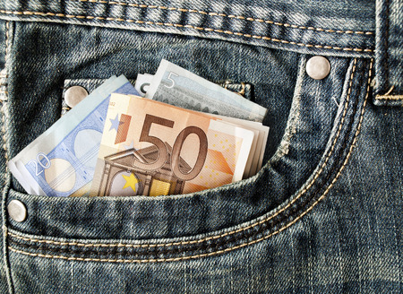 Banknotes in your pocket, euros in jeans. some banknotes in the pocket of jeans photo