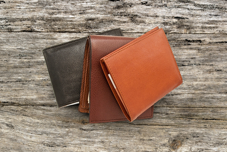 leather bag: leather wallet with money, some leather purses, three purse with paper money on the table Stock Photo