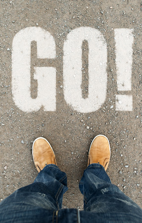 man on a tarmac road with the word go. A concept of movement photo