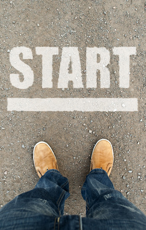 man op een geasfalteerde weg met het woord Start. Een concept van het uitgangspunt.