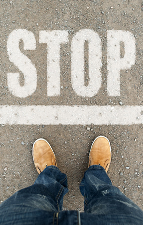man on a tarmac road with the word Stop. Stopping human way. man standing in front of the word stop photo