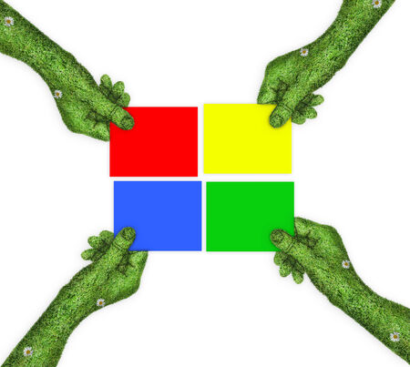 four hands: four colored sheet of paper in their hands. four hands holding four parts of the image. hand covered with green grass Stock Photo