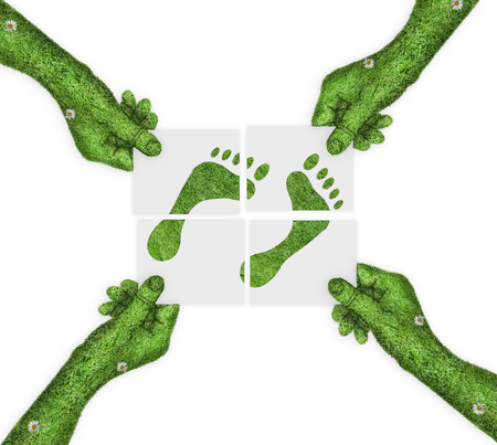 four hands: Human footprints on paper.  four hands holding four parts of the image. hand covered with green grass