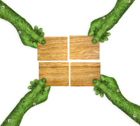 four hands: four wooden plate in his hands.. four hands holding four parts of the image. hand covered with green grass