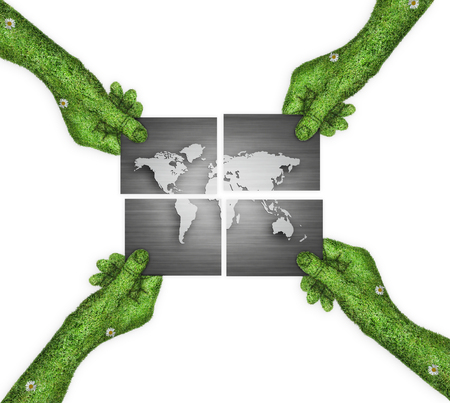 four hands: The world map is divided into four. four hands holding four parts of the image. hand covered with green grass Stock Photo