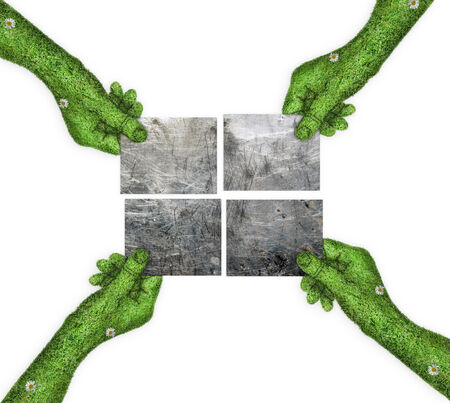 four hands: four metal plates in his hands. four hands holding four parts of the image. hand covered with green grass
