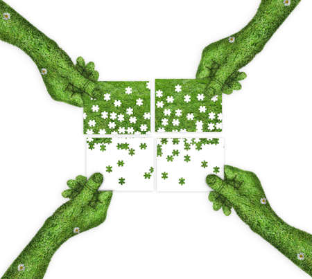four hands: four hands holding four parts of the image. hand covered with green grass. Puzzles in the hands of the people. ecology concept Stock Photo
