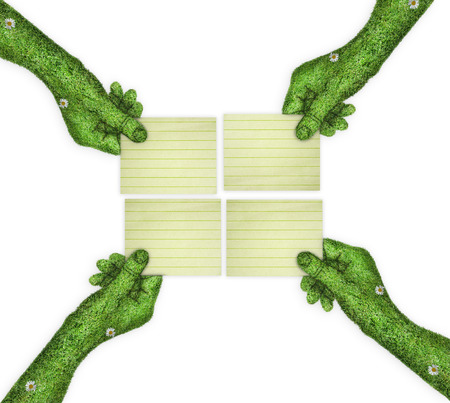 four hands: four clean sheets of paper in his hands. four hands holding four parts of the image. hand covered with green grass Stock Photo