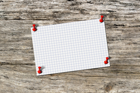 red pushpin: Blank paper memo on wood with red pushpin.