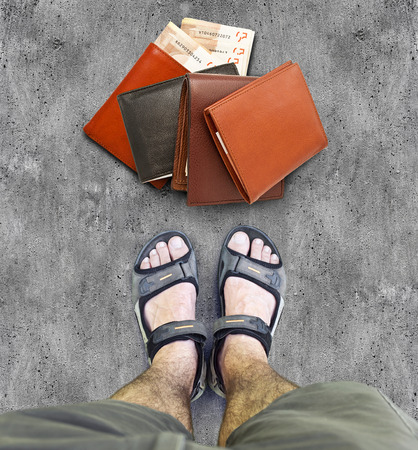 lost money: Black sandals on the road. Four purses with paper money. Lost wallet lying on the road Stock Photo
