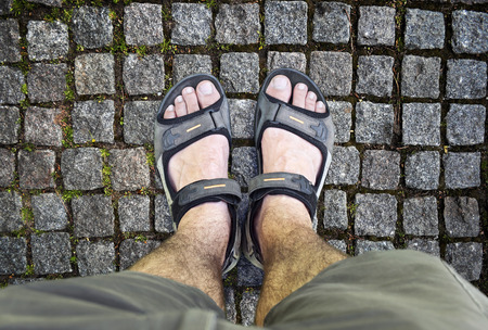 Black sandals on the road. A man standing on the road in black sandals photo