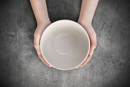 Honger concept. Vrouw die lege bord wachten voedsel. Lege plaat in de hand