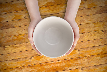 Hunger concept. Female holding empty plate waiting food. Empty plate in hand