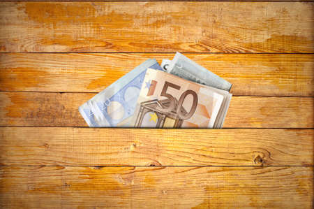 several: Several euro banknotes on a wooden table