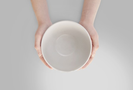 food concept: Hunger concept. Female holding empty plate waiting for food isolated. Empty plate in hand Stock Photo