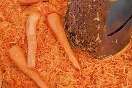 marchewka: Startej marchewki z tarką na stole. Makro marchew i tarka