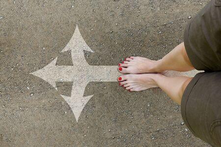 Vrouwelijke voeten op de grondweg. Meisje staat blote voeten op de weg met pijl naar voren. Stel je voeten op de top. Conceptuele foto, perspectief perspectief.