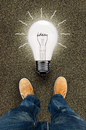 leather shoes: A man standing in front of a bulb symbol. Legs man in a yellow leather shoes
