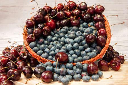 scattering: Fresh blueberries and cherries in basket