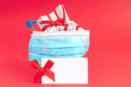 购物手推车与礼物在一个保护面罩在红色背景与注意模拟。在流感期间购买节日礼物的概念。