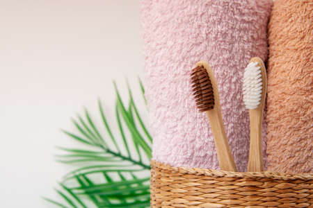 Bamboo toothbrushes with towels in a wicker wooden basket and palm leaves with copy space on white background. Spa, healthy lifestyle and ecology concept. 版權商用圖片 - 157436399