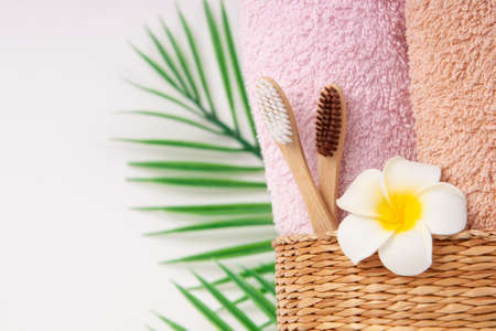 Bamboo toothbrushes with towels in a wicker wooden basket and palm leaves and plumeria flower with copy space on white background. Spa, healthy lifestyle and ecology concept. 版權商用圖片