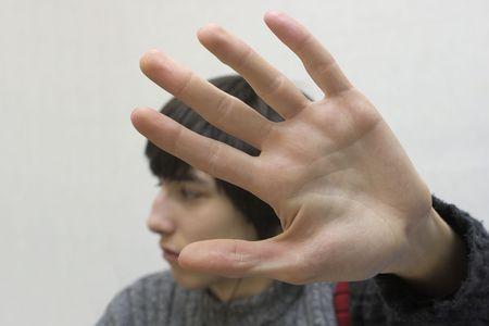 Nastolatek ukrywa twarz w ręce.