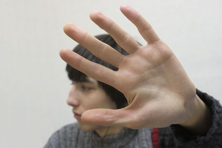 Teenager hides his face by hand.  photo