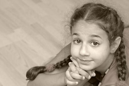 coquettish: The happy coquettish girl with plats. Sepia.