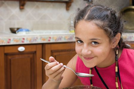 coquettish: Coquettish girl eating soup.  Stock Photo
