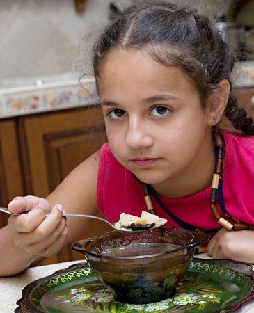 nespokojen: Dissatisfied girl eating soup Reklamní fotografie
