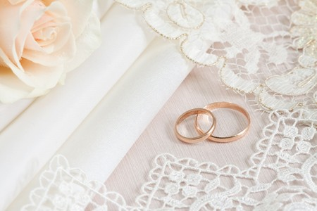 rose ring: Wedding fabrics and lace and two gold rings.