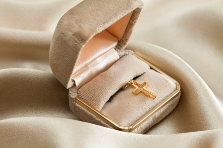 god box: Golden cross in a box over beige background. Stock Photo