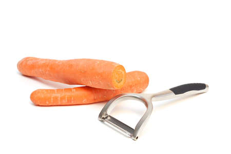 A carrot peeler and carrots isolated on a white background.  photo