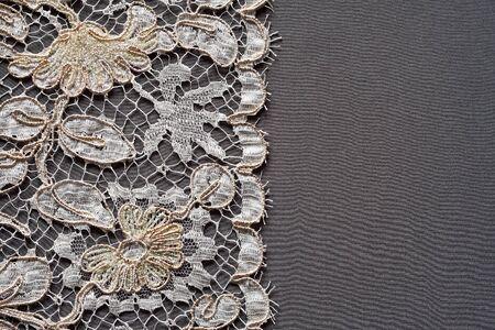 silk fabric: White lace on the dark grey silk background. Stock Photo