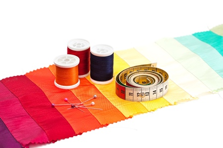 Bobbins of thread and tape measure on light background. photo