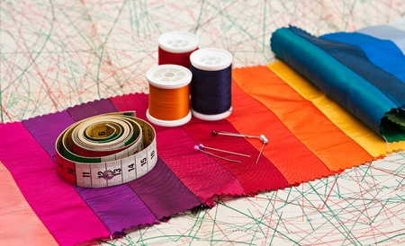 Bobbins of thread and tape measure on paper sewing pattern. photo