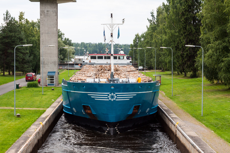 Chiatta con legno passa attraverso una chiusa in Finlandia. Archivio Fotografico - 86147979