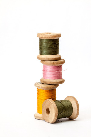 Old wooden coils of thread isolated on a white background. Stock Photo