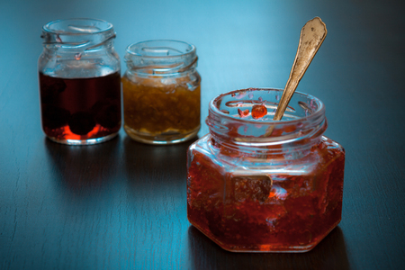 Glass jar of red jam with spoon on dark background. Stock Photo
