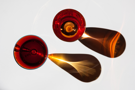 Two red glasses with interesting shadows on white. Archivio Fotografico