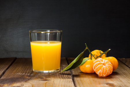 Glass of orange juice and tangerines with leaves on rustic wooden background. Still life with space for text. Stockfoto