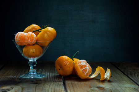 Tangerines (mandarins, citrus fruits) with leaves in glass on rustic wooden