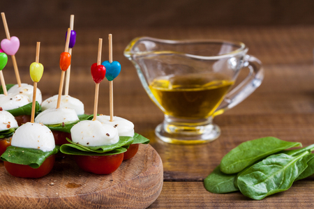Refreshment with cherry tomatoes, mozzarella and spinach on a wooden board.
