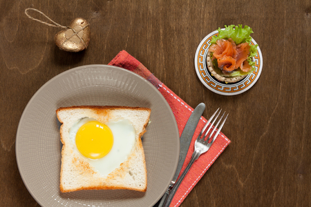 Breakfast with heart fried eggs and salmon tartlet. Foto de archivo